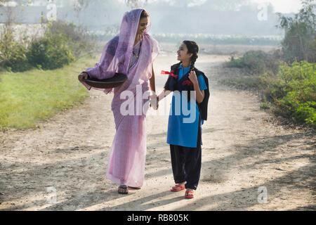 La productrice ou rural femme marche sur village-rue, avec sa fille va à l'école portant un fer à repasser gold pan. Photo Stock