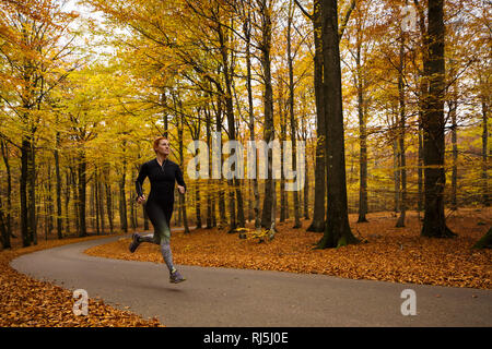 Young woman running through forest Photo Stock