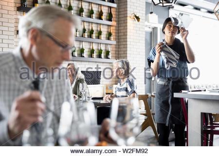 Serveuse en restaurant nettoyage des verres à vin Photo Stock