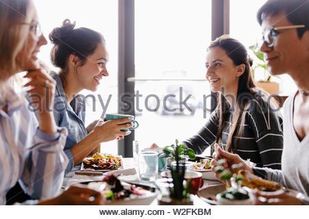 Heureux les femmes amis manger dans restaurant Photo Stock