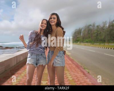 Deux femmes se tenant ensemble sur un sentier au bord de mer Photo Stock