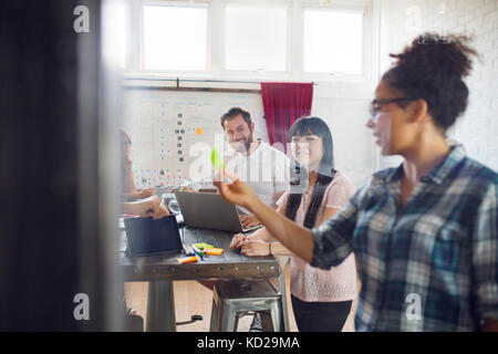 Smiling collaborateurs dans office, woman gesturing Photo Stock
