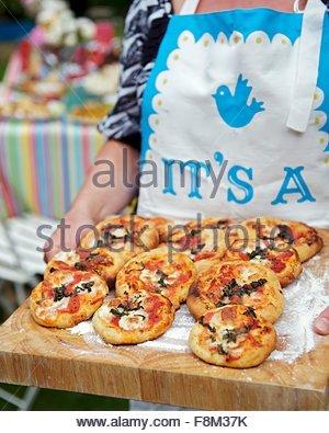 Femme tenant un mini-pizzas sur planche de bois Photo Stock