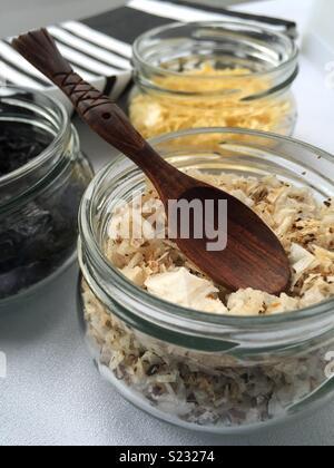 Gros plan d'un bocal en verre avec champignons aromatisés et une cuillère en bois. Deux autres bols sont volontairement un peu en dehors de l'accent principal derrière le bocal en verre. Photo Stock