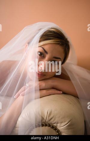 Portrait de mariée appuyée sur un canapé en cuir Photo Stock