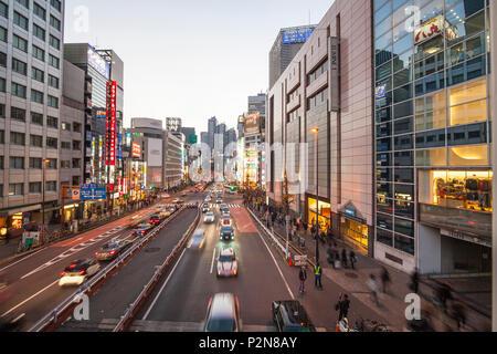 Koshu Kaido rue avec le Park Hyatt, panneaux publicitaires et des voitures en mouvement à l'heure bleue, Shinjuku, Tokyo, Japon Photo Stock