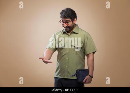 Homme portant lunettes tenant un petit sac dans une main et en regardant son Palm en surprise. Photo Stock