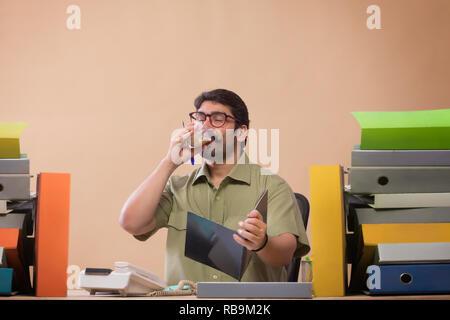 Les fichiers d'affaires d'étudier tout en sirotant un verre de thé assis à son bureau en bureau. Photo Stock