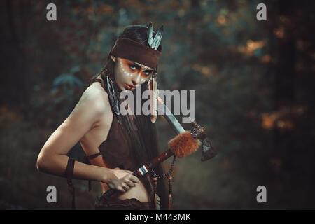 American Indian Warrior avec tomahawk. Arrière-plan de la forêt Photo Stock