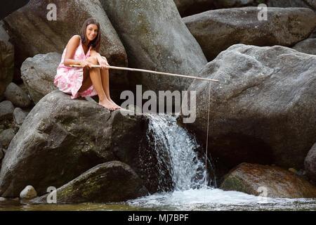 Souriante jeune fille assise sur un rocher à la pêche. Vous pourrez vous détendre en plein air Photo Stock