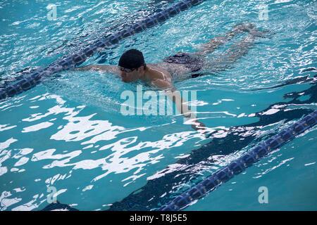 L'homme nage dans une piscine Photo Stock