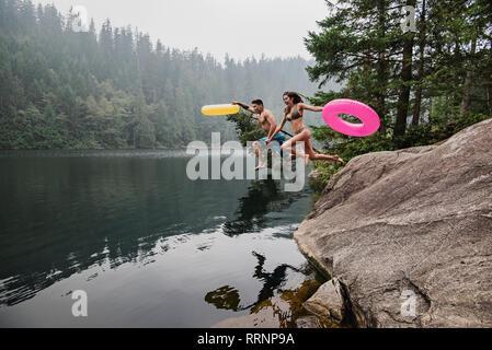 Jeune couple ludique avec anneaux gonflables sauter dans le lac à distance, Squamish, British Columbia, Canada Photo Stock