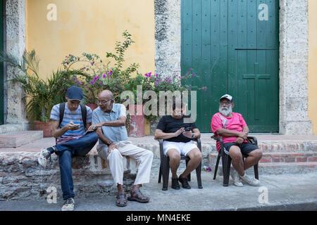Les hommes de vérifier leurs téléphones portables , Getsemani, Carthagène, Colombie, Amérique du Sud Photo Stock