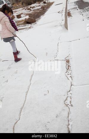 Petite fille de cinq ans fait glisser un bâton à travers la neige fraîche, ce qui fait une ligne Photo Stock