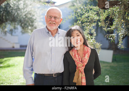 Older couple smiling in backyard Photo Stock