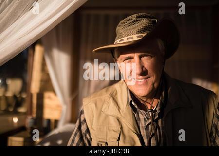 Portrait of smiling man sitting on lit à baldaquin Photo Stock