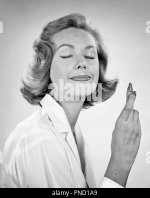 Années 1950 Années 1960 WOMAN SMILING EYES CLOSED QUI SOUHAITENT AVEC LES DOIGTS CROISÉS - g4567 HAR001 HARS, MESDAMES LES PERSONNES QUI DÉSIRENT B&W EXPRESSIONS CHANCE RÊVES OBJECTIFS LA PROTECTION DE L'ESPOIR DU BONHEUR LA CHANCE SOURIT tiens tiens IMPLORE JOYEUX DÉSIR MI-PROMETTEUSES DES PROFILS MID-ADULT WOMAN SOUHAIT D'ORIGINE ETHNIQUE CAUCASIENNE EN NOIR ET BLANC LES YEUX FERMÉS HAR001 old fashioned Photo Stock
