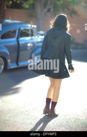 Adolescente marcher dans la rue ensoleillée, avec voiture ancienne porte ouverte légèrement. Photo Stock