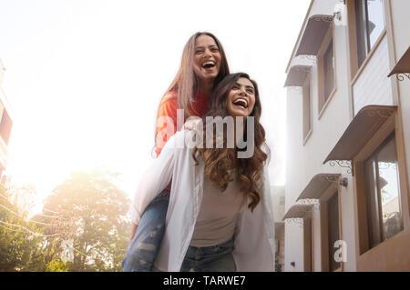 Ami femme portant sur son dos la marche à l'extérieur dans une rue Photo Stock