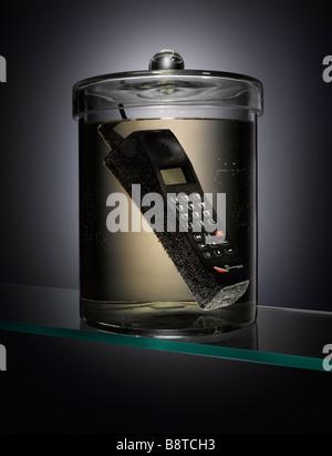 Un vieux téléphone dans un bocal échantillon Photo Stock