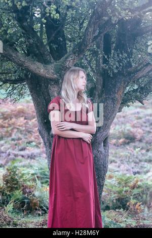 Une femme blonde avec une robe rouge est debout sous un arbre Photo Stock