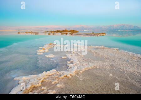 Israël, au sud du district, Ein Bokek. Formations de sel sur la mer Morte au coucher du soleil. Photo Stock