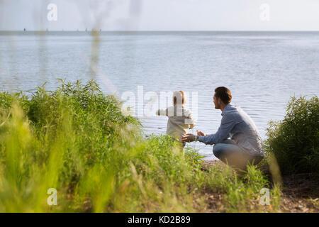 Père avec son (18-23 mois) par la mer Photo Stock
