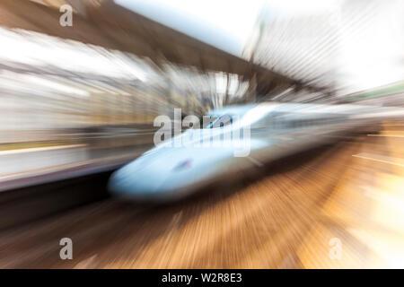 Blurred motion view of bullet train Shinkansen à la plate-forme de la gare de Tokyo, Japon. Photo Stock