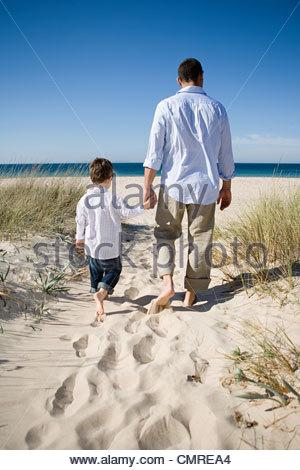 Père et fils walking on beach Photo Stock