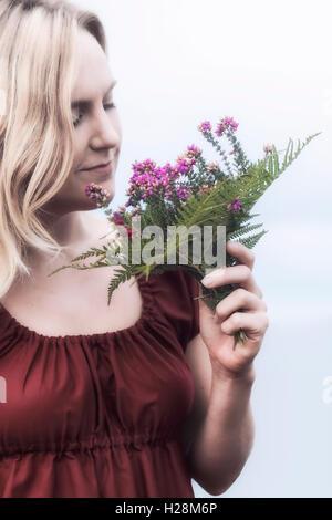 Portrait d'une femme blonde avec un bouquet de fleurs de bruyère Photo Stock
