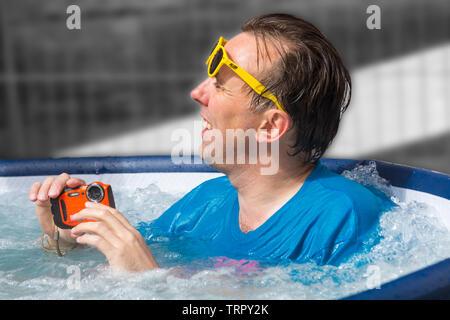L'homme de vous détendre dans le bain à remous à Bournemouth, Dorset UK en Juin Photo Stock