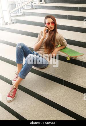 Femme assise sur les marches avec skateboard talking on mobile phone Photo Stock