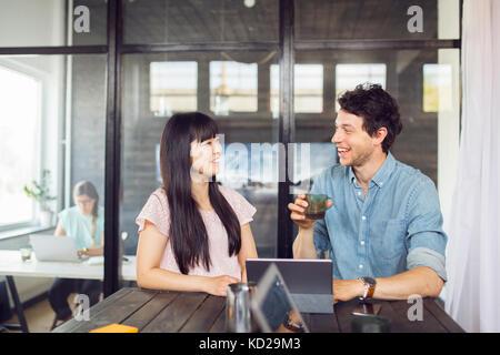 Coworkers talking and smiling, femme travaillant en arrière-plan Photo Stock