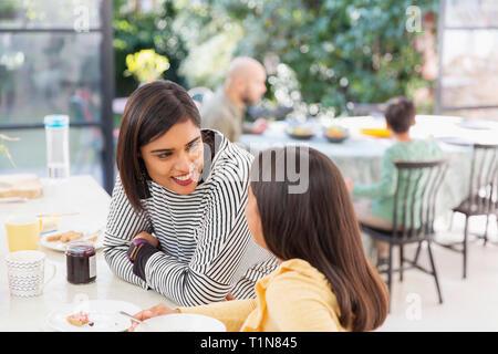 Mère et fille de parler, manger le petit déjeuner Photo Stock