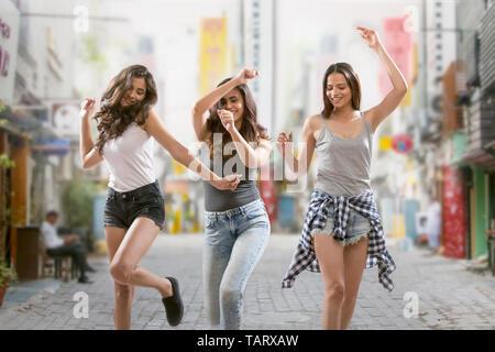 Trois girl friends having fun dancing on street Photo Stock