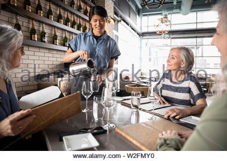 Les femmes âgées amis waitress in restaurant Photo Stock