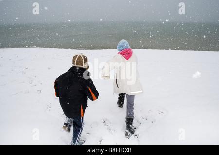 Les enfants s'exécutant sur une plage enneigée Photo Stock