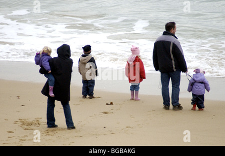 Famille sur la plage face à la mer Photo Stock