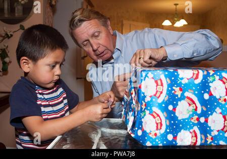 Jeune enfant cadeau de Noël d'enrubannage. Avec l'aide de papi Série de 7 images. M. © Myrleen Pearson ...Ferguson Cate Photo Stock
