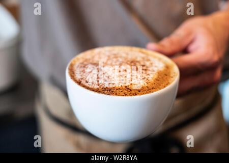 High angle fermer op de personne tenant tasse de Cappuccino. Photo Stock