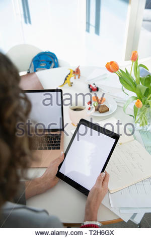Businesswoman with digital tablet travaillant à domicile Photo Stock