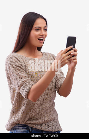 Woman looking at mobile phone avec expression surprise Photo Stock