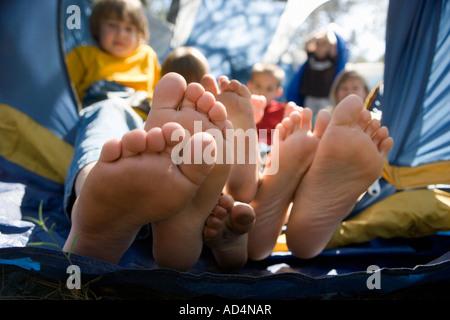 Vue sur les pieds des enfants poussant hors de la tente Photo Stock