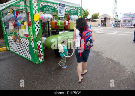 Jeune enfant sur une laisse promenades à travers State Fair Grounds avec mère, à côté d'un stand de cornichon. Photo Stock