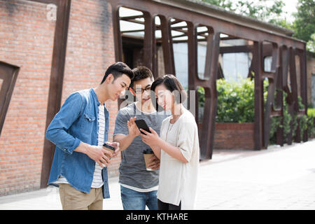 Cheerful young friends using smart phone Photo Stock