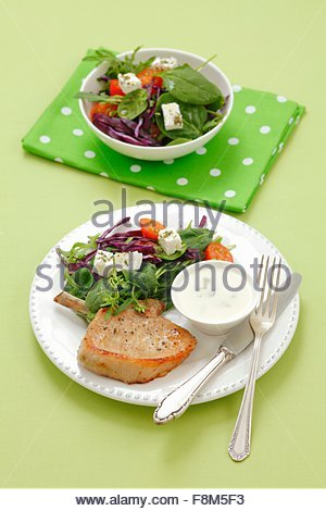 Une côte de porc avec une salade de légumes, fromage feta et d'une trempette au yogourt Photo Stock