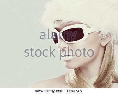 Jeune femme portant des lunettes de soleil et chapeau de fourrure blanche Photo Stock