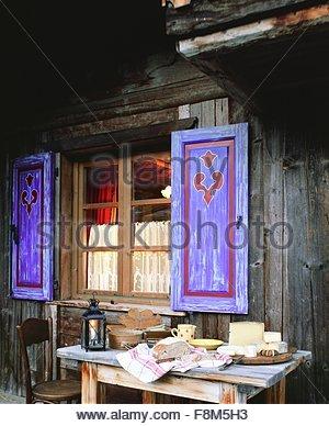 Divers fromages alpins français à l'extérieur d'un chalet en bois Photo Stock