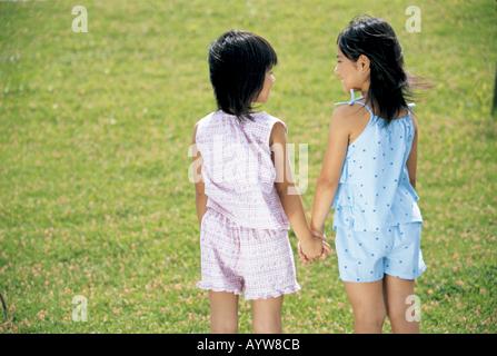 Deux jeunes filles se tenant la main les uns les autres Photo Stock