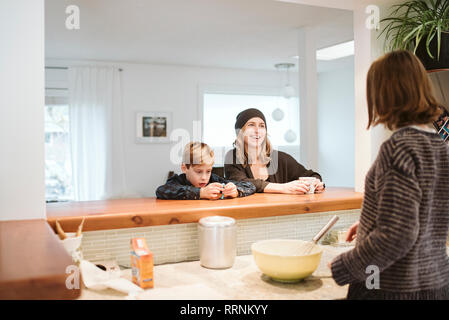 La cuisson de la famille et de parler dans la cuisine Photo Stock